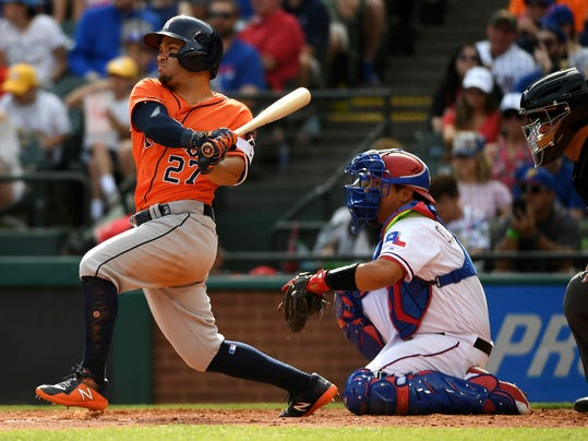 Houston Astros' Jose Altuve (27) follows through on a single as Texas Rangers catcher Juan Centeno and home plate umpire Ed Hickox look on in the fifth inning of a baseball game, Saturday, March 31, 2018, in Arlington, Texas. Houston won 9-3. (AP Photo/Jeffrey McWhorter)