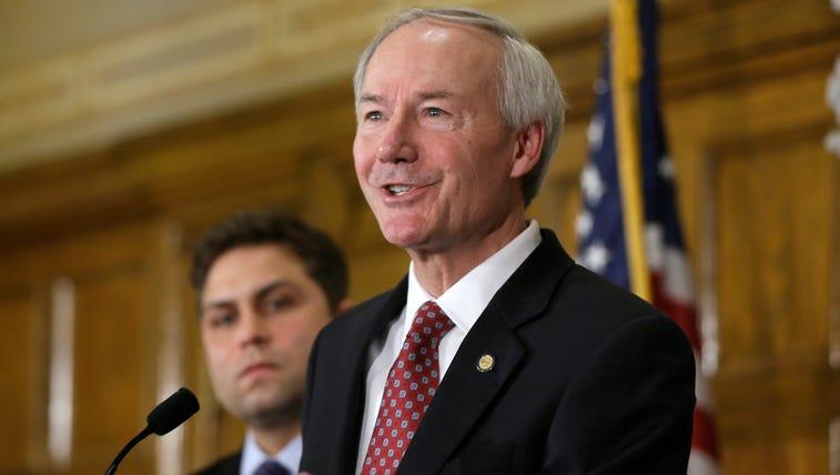 Arkansas Gov. Asa Hutchinson, right, answers reporters'