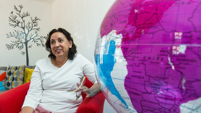 Adventure Travel owner Wanda Mattiace sits next to a huge globe on display in her new office on Wednesday, May 25, 2016. The office is located at 2340 Avenida de Mesilla.
