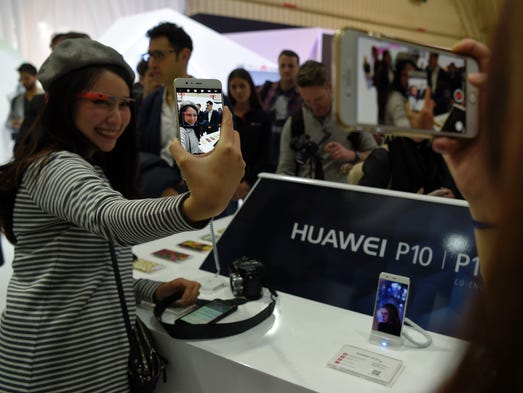 Journalists check the new model of the Huawei phone