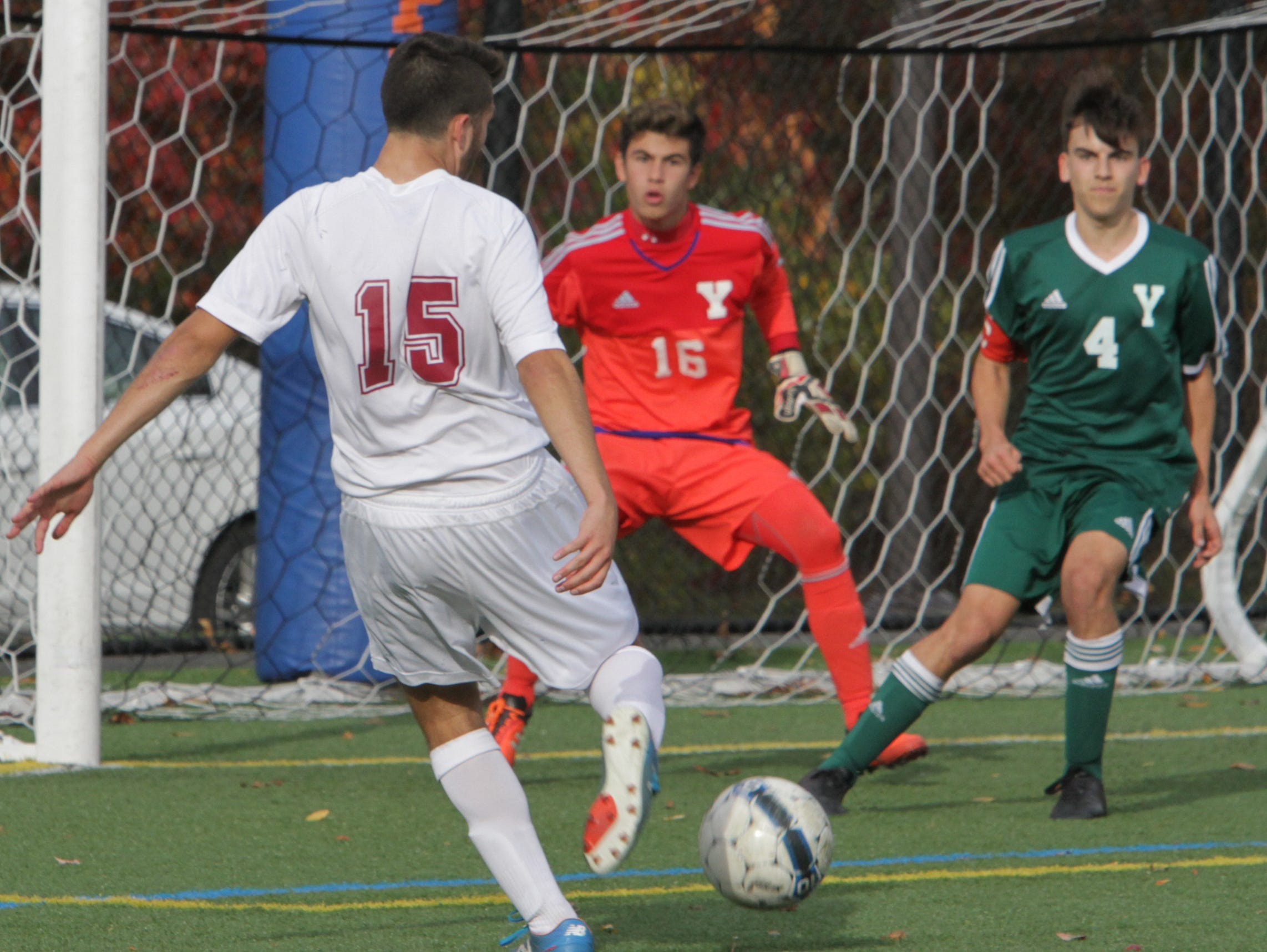 Yorktown defends against a shot by Tristan Elwes of Scarsdale during their Class AA boys soccer semifinal at Purchase College Oct. 29, 2105.
