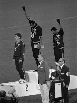Extending gloved hands skyward in racial protest, U.S. athletes Tommie Smith, center, and John Carlos, right, stare downward during the playing of the Star Spangled Banner after Smith received the gold and Carlos the bronze for the 200 meter run at the Olympics in Mexico City on Oct. 16, 1968.