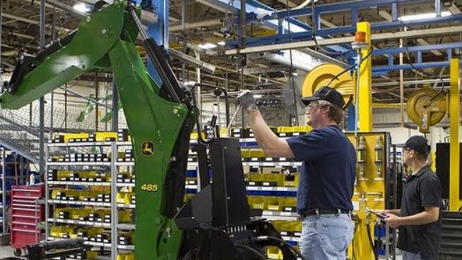 Amerequip employees work on machinery for John Deere at the company's Kiel plant.