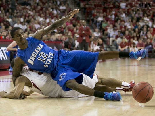 Indiana State guard Dawon Cummings (12) and Arkansas guard Rickey Scott (3) fall to the ground as they both dive for a loose ball during the first half of an opening round National Invitational Tournament NCAA college basketball game in Fayetteville, Ark., Tuesday, March 18, 2014. (AP Photo/Gareth Patterson)