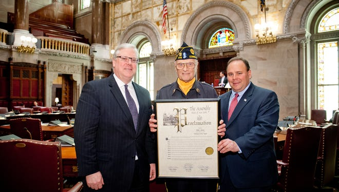State Sen. Tom O'Mara, left, and Assemblyman Phil Palmesano, right, present a copy of an adopted resolution to Schuyler County resident Philip J. Swaney Sr. in the New York State Senate chamber.