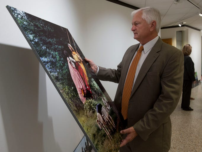 Pensacola State College President Edward Meadows looks over selected works by photographer Steven McCurry at the college's visual arts gallery Thursday afternoon. The administrators was looking for possible candidates to add to PSC's new outdoor art gallery.