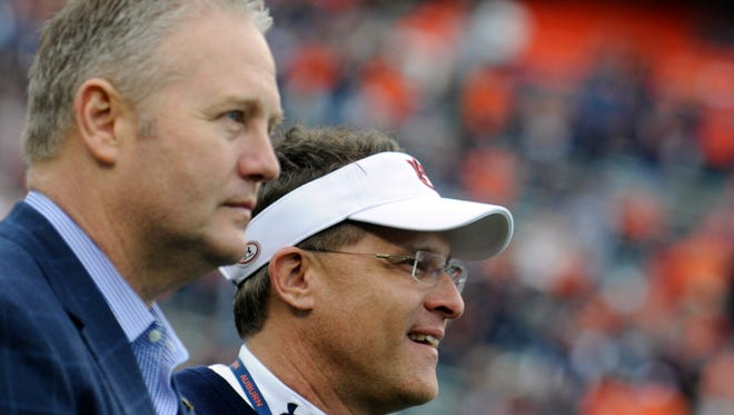 Auburn Athletic Director Jay Jacobs (left) and head coach Gus Malzahn watch highlights from the 2013 season as the 2013 team receives their SEC Championship rings during the A-Day game at Jordan-Hare Stadium Saturday, April 19, 2014, in Auburn, Ala.