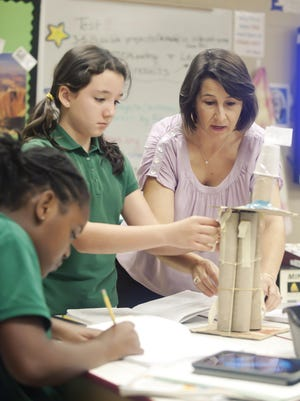 St. Anthony Catholic School teacher Vicki Moorehead talks with students Adriana Terrazas, standing, and London Coleman about their building engineering project. Moorehead is a recipient of the Presidential Awards for Excellence in Mathematics and Science Teaching. St. Anthony is the first school in the state to receive AdvancED STEM certification from the State of Mississippi.