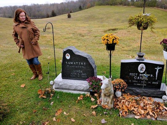 Debbie Larsen walks past the graves of her sister