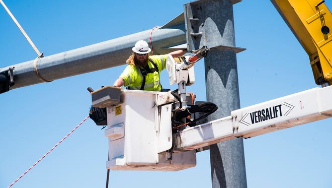 A worker reaches for a tool as he secures the mast arm of a traffic signal