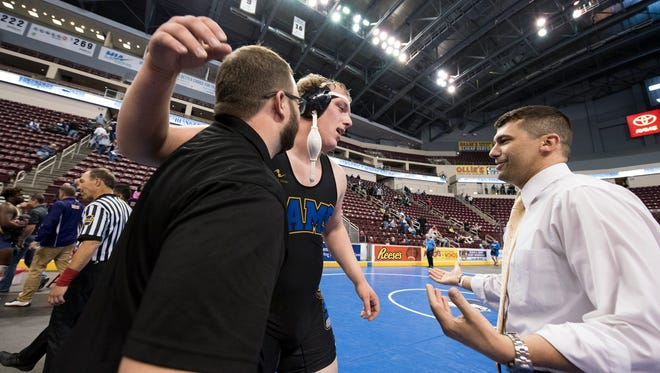 Kennard-Dale's Tanner Harkins hugs his coaches after winning his 285-pound championship at Hershey's Giant Center for the District 3 tournament, Saturday, Feb. 24, 2018.