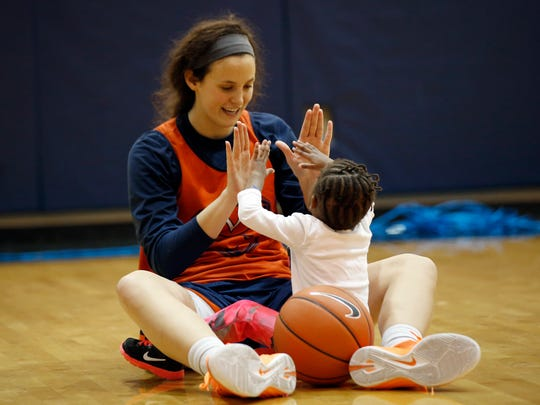 "In this Jan. 27 photo, University of Virginia basketball player Sarah Beth Barnette plays with Ngoty, the adopted daughter of Virginia women's basketball coach Joanne Boyle in Charlottesville. When the team travels, Ngoty often goes along, riding with the players and her mom. On one recent two-hour bus trip home from Virginia Tech, Ngoty sat on Boyle's lap, watching ""The Jungle Book"" on an iPad as Boyle watched game film on her laptop."