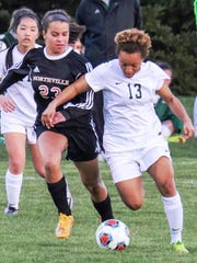 Novi's Chloe Allen (right) dribbles up field against