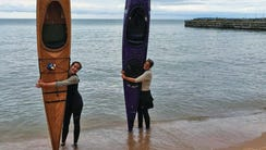 Sophie Goeks (left) and Uma Blanchard hug their kayaks