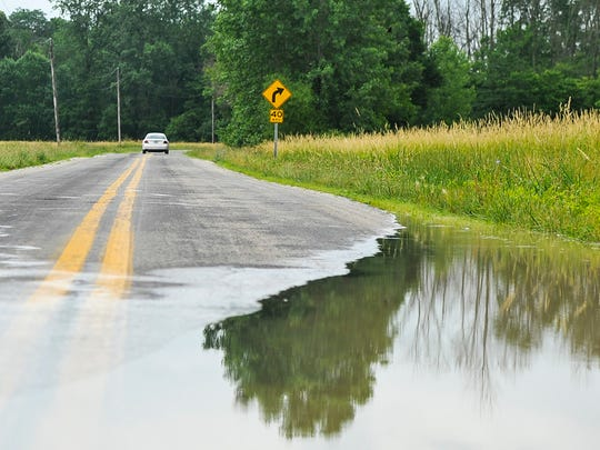 A car turns back after encountering deep water on Larue Green Camp Road East on Thursday morning. Heavy rains Wednesday night and early Thursday morning flooded some areas of Marion County, however by afternoon most flooded areas dried up.