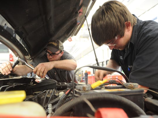 "MPTC automotive students Colton Elliott of Beaver Dam, left, and Nick Flasch of Mayville, work on a car in Moraine Park Technical College's auto shop. Instructors at the school say the industry is ""crying for high level students"" who are completing automotive technology and automotive technician programs."