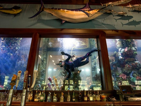 Renee Bellafato, of Bella Aquatics, cleans the 12,500 gallon saltwater aquarium in the Islamorada Fish Company at the Bass Pro Shop in Prattville, Ala., on Wednesday August 31, 2016.