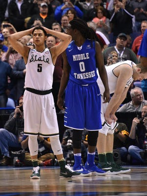 Bryn Forbes holds his head and Matt Costello bows his, as MSU falls to Middle Tennessee, 90-81, in the first round of the NCAA Tournament.
