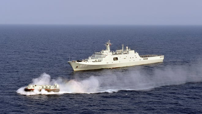 In this photo taken on Wednesday, March 20, 2013 released by China's Xinhua News Agency, China's amphibious ship Jinggangshan is seen during a coordination training with a hovercraft in waters near south China's Hainan Province, in the South China Sea. (AP Photo/Xinhua, Gan Jun) NO SALES ORG XMIT: XIN802