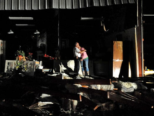 Jeff and Melissa McKenzie embrace in the ruins of their
