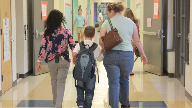 Parents and student make their way to class at South Topsail Elementary School. Pender County Schools will delay the in-person learning start by one day