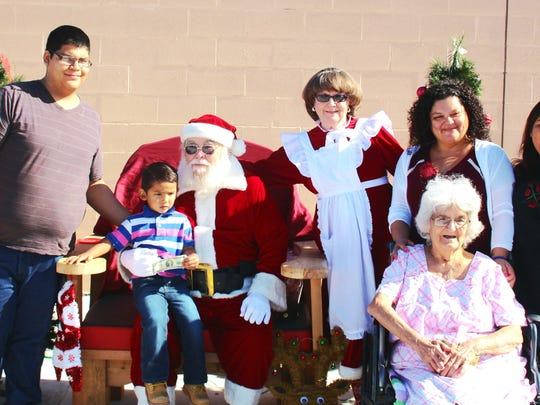 Mary Vrrastiqui, celebrating her 83rd birthday, with Santa and Mrs. Claus, Carlos Castillo, Arron Martinez, Stephanie Bermudez and Gabriella Castillo