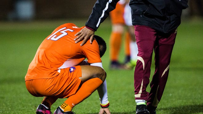 Clemson senior Alex Happi is patted on the back by a Denver player while mourning his team's lost against  Denver in an Elite 8 NCAA tournament game on Friday, December 2, 2016 in Clemson.