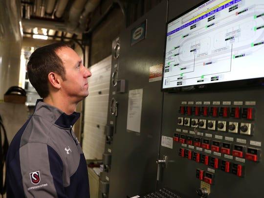 Facility Director Paul Golomski checks a console which