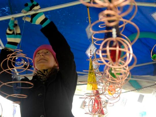 Artist Dru Perry hangs one of her pieces at the Cherokee