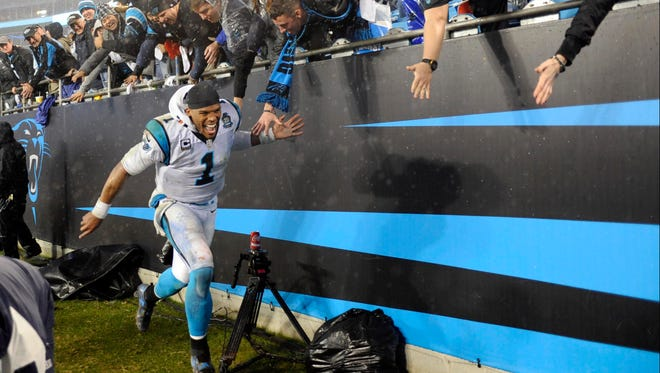 arolina Panthers quarterback Cam Newton celebrates with fans after beating the Arizona Cardinals in the wild-card round.