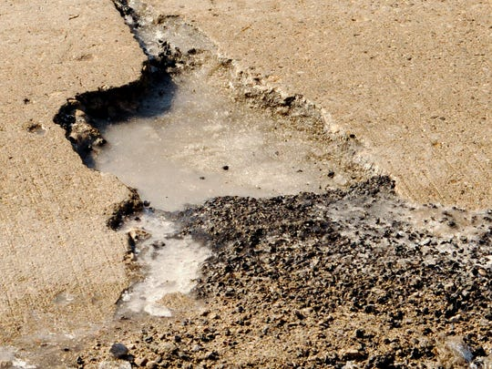 A large pothole on Waldo Boulevard before a street crew from the city of Manitowoc Department of Public Infrastructure applied asphalt cold patch to repair this pothole.