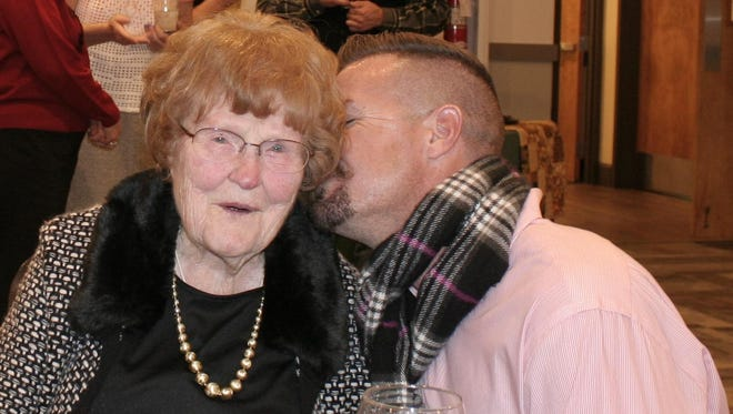 Benoit Beisser kisses his grandmother Barbi DiIaconi during her 100th birthday party Jan. 7 at Creekside Golf Club.