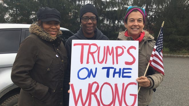 Colleen Channer of Scotch Plains, Pamela Brug of Westfield and Amalia Duarte of Mendham prepare to protest in front of Trump National Golf Club in Bedminster.