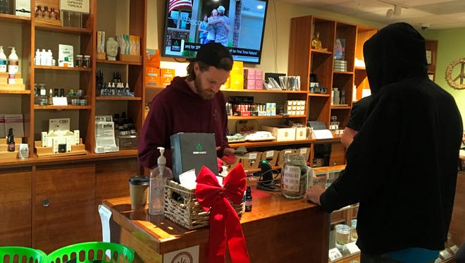 Torrey Holistics employee Matt Sullivan, left, handles a sale with a customer in San Diego, Calif., on Dec. 14, 2017. On Thursday, California issued its first batch of business licenses for the state's upcoming legal marijuana market, setting the stage for sales to begin in January.