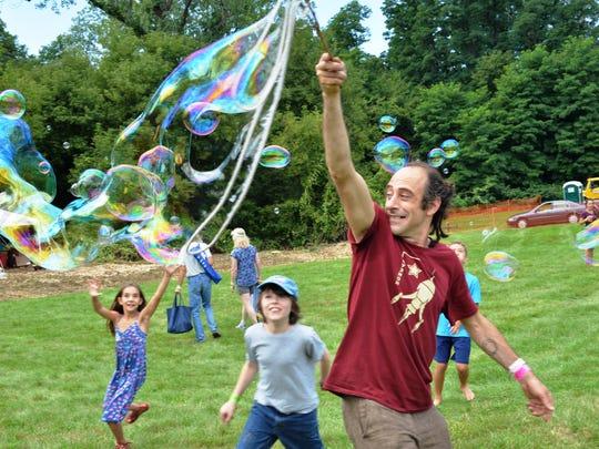 Phinneus Sonin of Burlington creates a large soap bubble for the children at the WYSIWYG Festival at Burlington College.