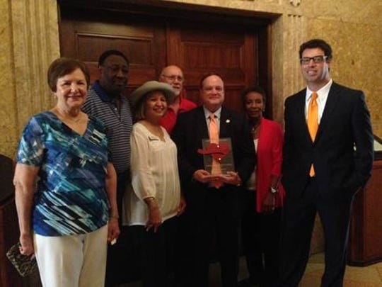 """AARP volunteer advocates honor Rep.  Robert Johnson (center, holding award) as a """"Capitol Caregiver."""" From left are Gayle Joseph, L.C. Thomas, Brenda Hatfield, Bobby Savoie, Johnson, Althea LaCour and Andrew Muhl."""
