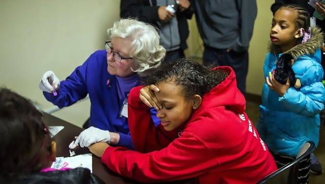 Amarria Jackson, 16, of Flint, looks away so she won't see blood as a health official in February 2016 takes her blood for a lead test at Carriage Town Ministries in Flint, Mich.