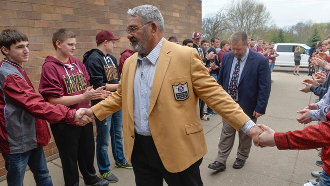 Royalton native NFL Hall of Famer Jim Langer shakes hands with members of the Royalton High School football team Wednesday, April 27. He was on his way to a ceremony designating the school's Langer Field, named after him, as one of only 97 high school football fields in the country as an NFL Hometown Hall of Fame field.