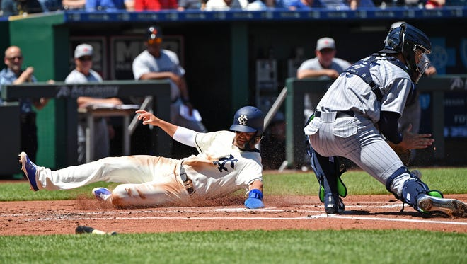 Royals' Whit Merrifield slides home for a run past Tigers catcher Grayson Greiner during the first inning Sunday in Kansas City.