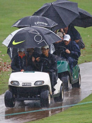 Standard bearers, caddies, officials, fans and golfers rush off the Country Club of Jackson golf course as a weather warning horn sounds during the resumption of Friday's second round of the Sanderson Farms Classic golf tournament, Saturday, Nov. 7, 2015, in Jackson, Miss. Play was suspended for the day with continuation of the second round extending to Sunday morning. (AP Photo/Rogelio V. Solis)
