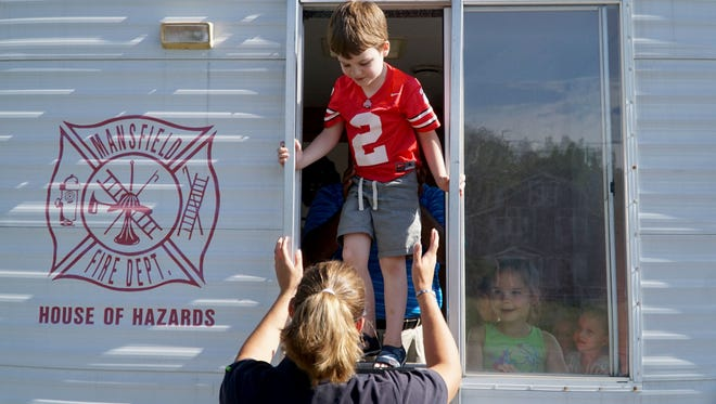 Owen Simmering, 5, escapes the House of Hazards with the help of Mansfield firefighter Jerica Barnett on Tuesday during a Safety Town lesson.