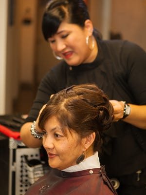 In this file photo, Leilani San Nicholas watches through a mirror as Beverly Jesus of Couture Beauty Salon applies finishing touches to her hair during a makeover.