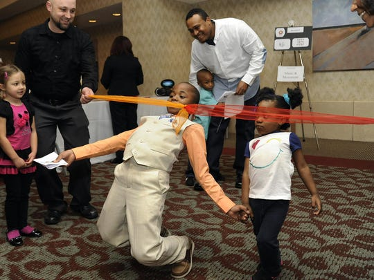 """Detroit residents Brandon Holmon, 7, and his sister, MaKayla Johnson, 3, do the limbo during the seventh Annual """"An Evening With Dad"""" event at the Edward Village Hotel."""