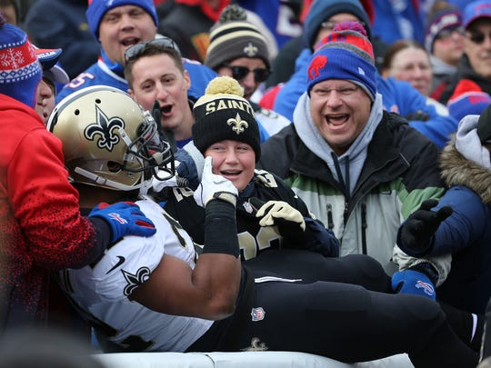 Saints Mark Ingram jumps into the stands after 1 of his 3 touchdowns against the Bills.