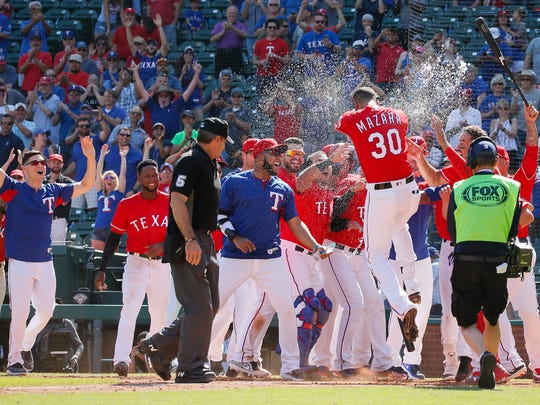 Texas Rangers right fielder Nomar Mazara (30) is greeted at home plate by teammates after hitting a walk off solo home run in the 10th inning against the Detroit Tigers at Globe Life Park in Arlington on May 9, 2018.