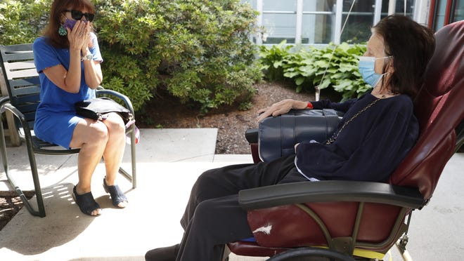 Marcie Abramson, left, becomes emotional as she speaks to her mother, Cynthia, outdoors at the Hebrew Rehabilitation Center, Wednesday June 10 in Boston, under the state's new nursing home visitation guidelines which requires social distancing. The two haven't been able to visit in person since March.