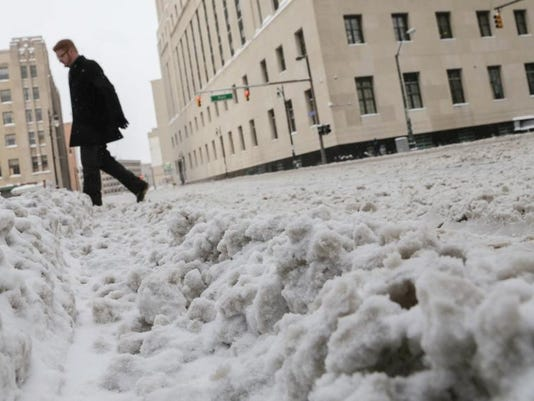 A man walks through the slushy streets of downtown Detroit on Thursday January 2, 2014 near the intersection of First