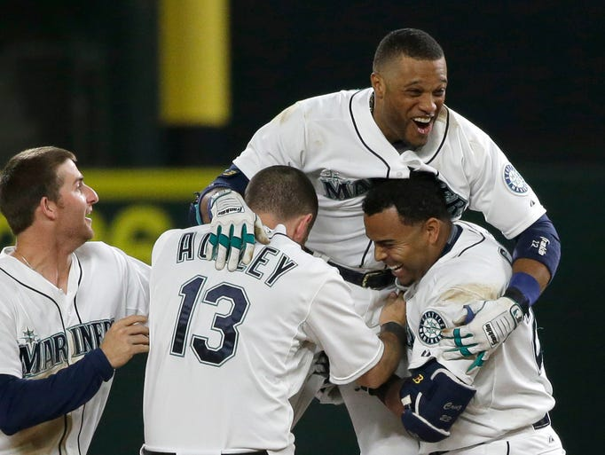Seattle Mariners' Robinson Cano, upper right, is lifted