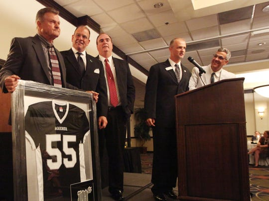 Keynote speaker Michael McNerney, left, former principal of Mariner High School, was presented with a framed Mariner jersey during the LCAC Hall of Fame Banquet at Crowne Plaza Hotel on Sunday.