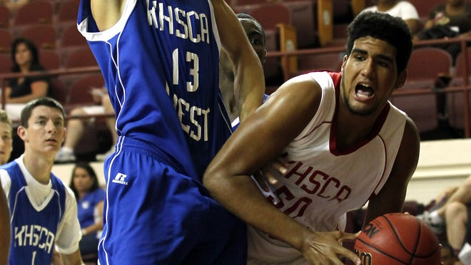 East's Trey Moses (50) fights to get his shot off under pressure from West's Chase Shellman (13) during the Kentucky High School Coaches Association Boys East / West Junior All-Star Basketball game at Bellarmine University in Louisville, Kentucky.       June 21, 2014